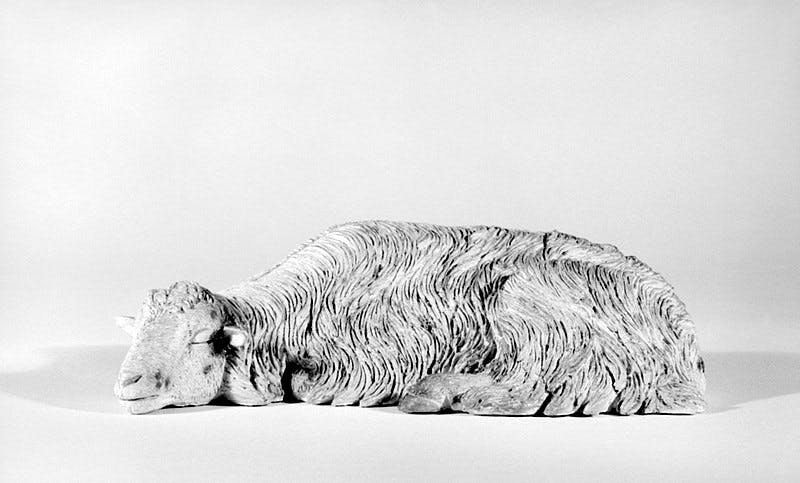 A metal and ceramic sculpture of a sleeping sheep on a white background.