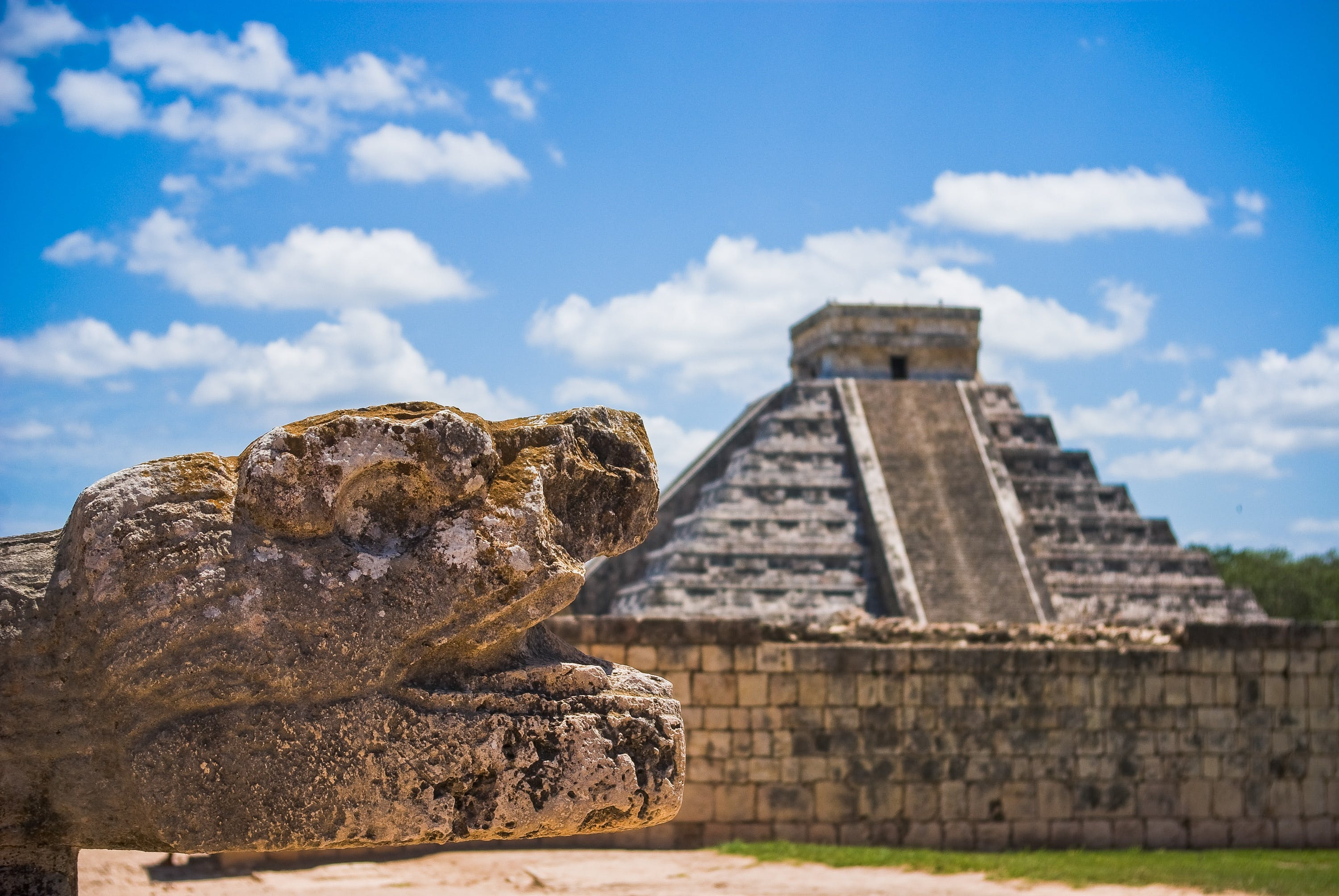 A photo of a stepped Mayan pyramid with a weathered stone sculpture of a serpent's head in the foreground.